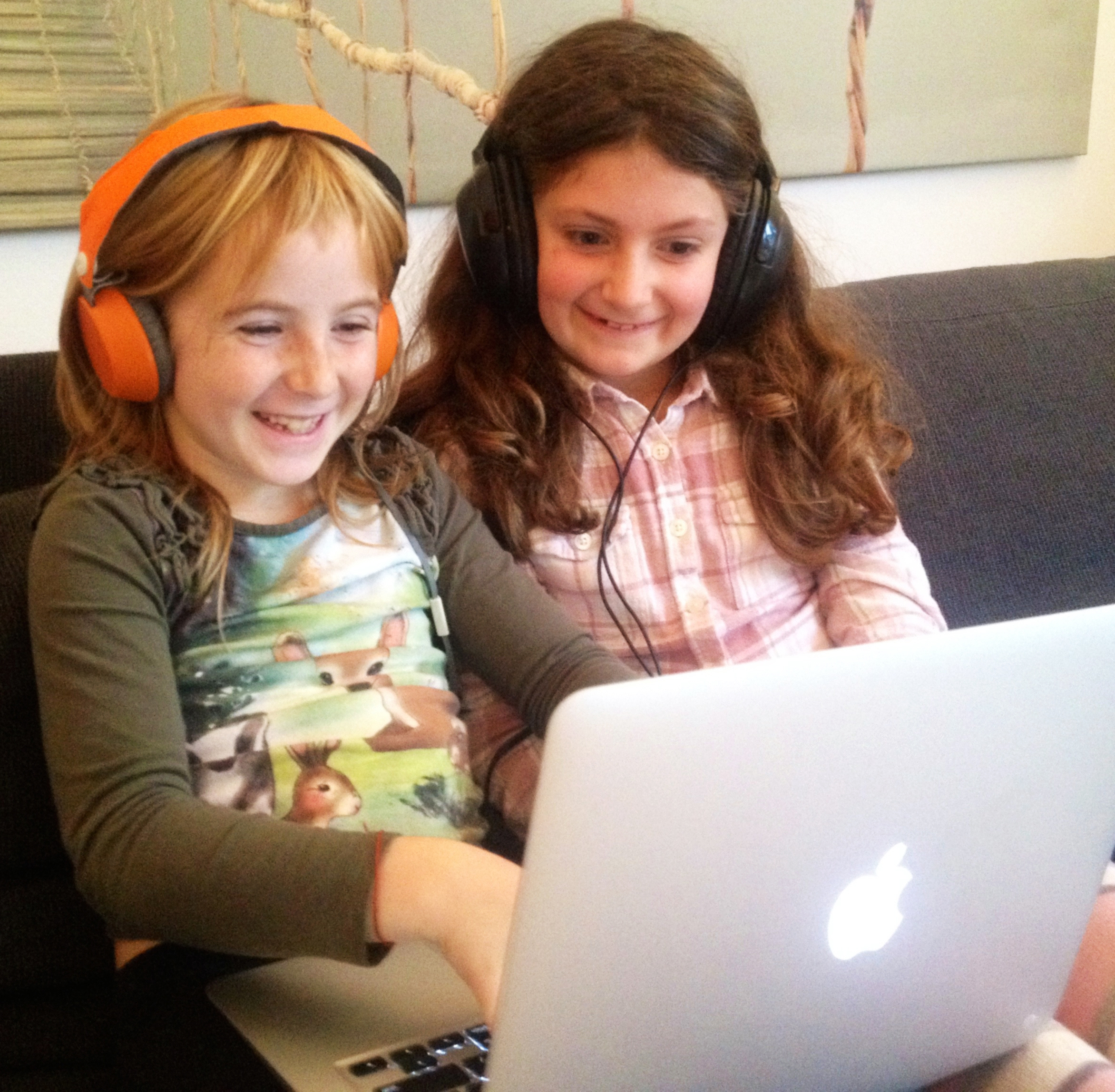 Two children playing a computer game together wearing headphones.
